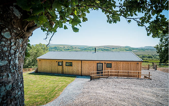 Wooden cabin overlooking the green rolling hills of Wales