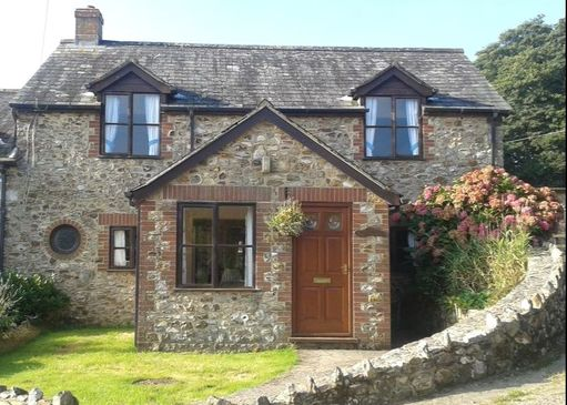 cobble cottage with wooden windows and a wooden door
