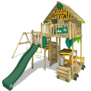 A large wooden playhouse high up on stilts with a slide coming out of the playhouse and a sandpit underneath