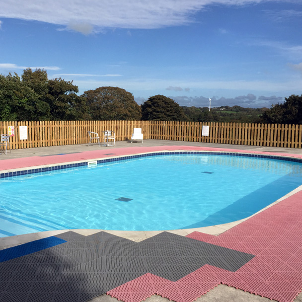 Outdoor swimming pool with pink snow slip mats around the edge
