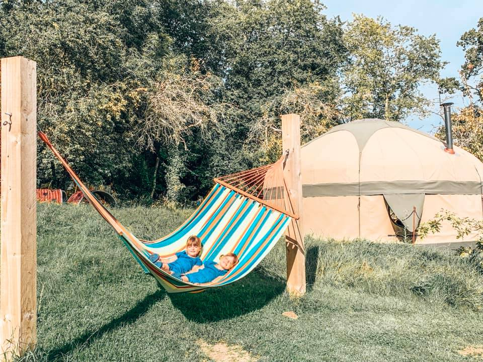 Two children relaxing in the hammock at campden yurts
