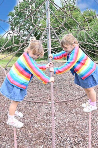 two girls balancing on a spiders web climbing frame waring blue skirts and rainbow jumpers