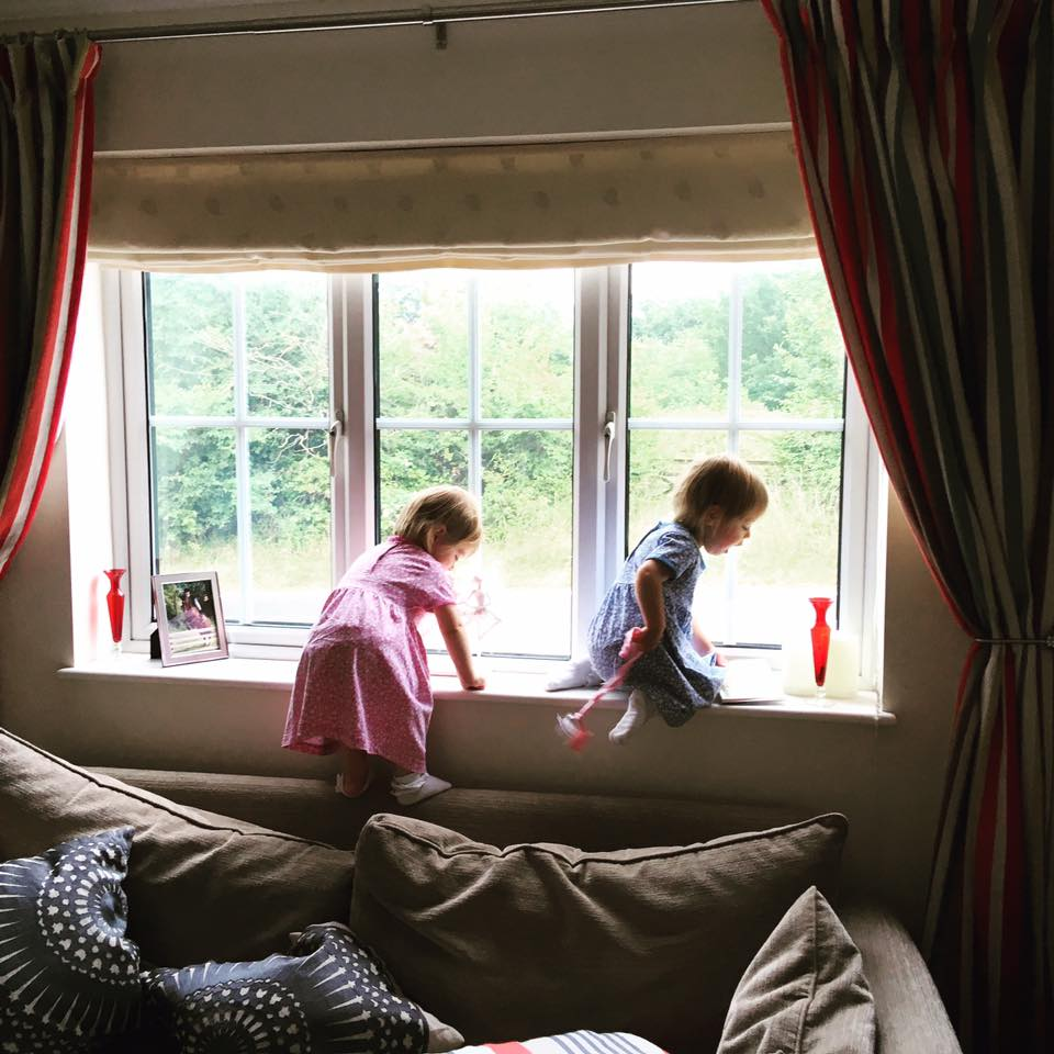 two girls climbing on the back of the sofa looking out of the window