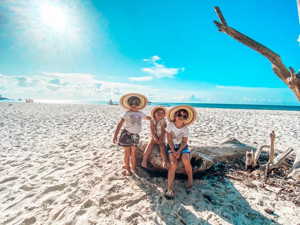 Three Children sitting on a long on Watamu family friendly beach