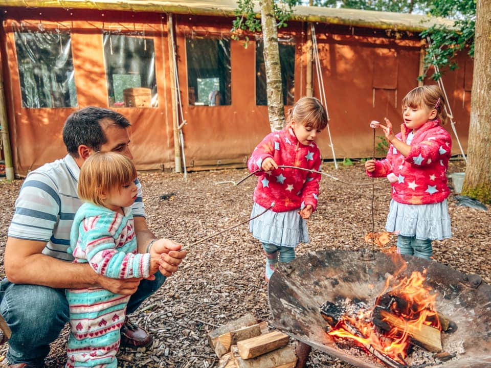 three children and a daddy around the campfire toasting marshmallows