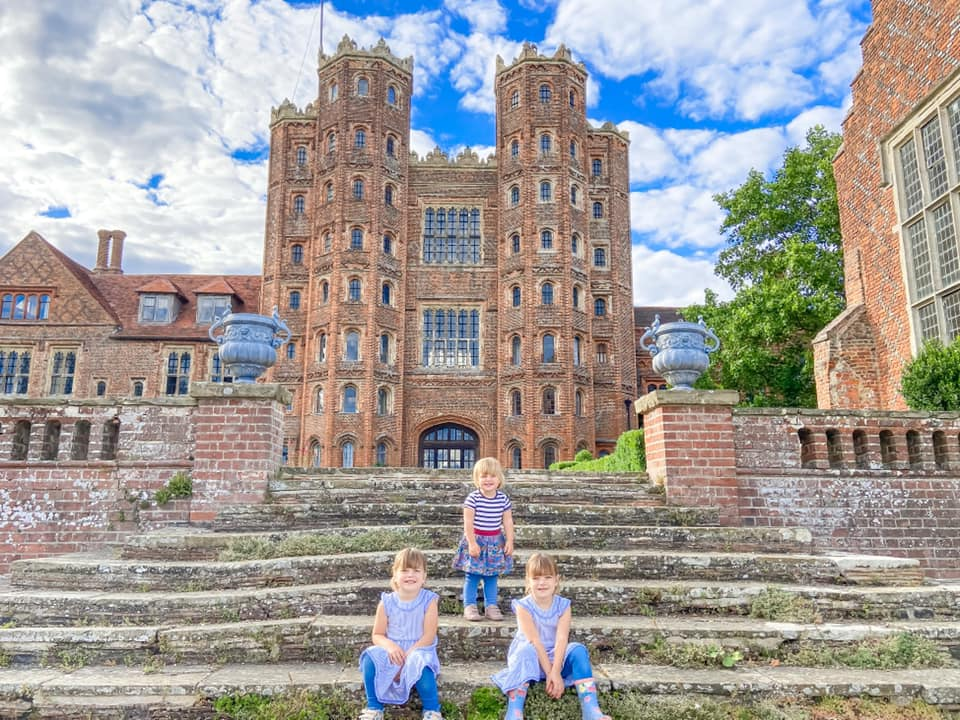 Three children sitting on the steps of layer marney tower in essex