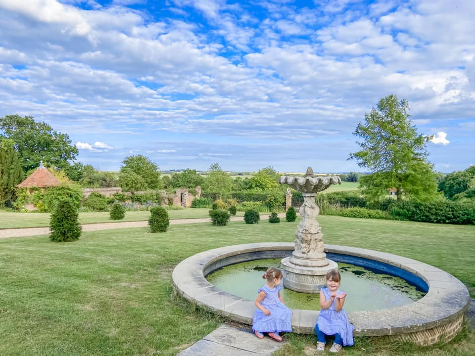 two girls in blue dresses sitting on the fountain in the Laye marney tower estate