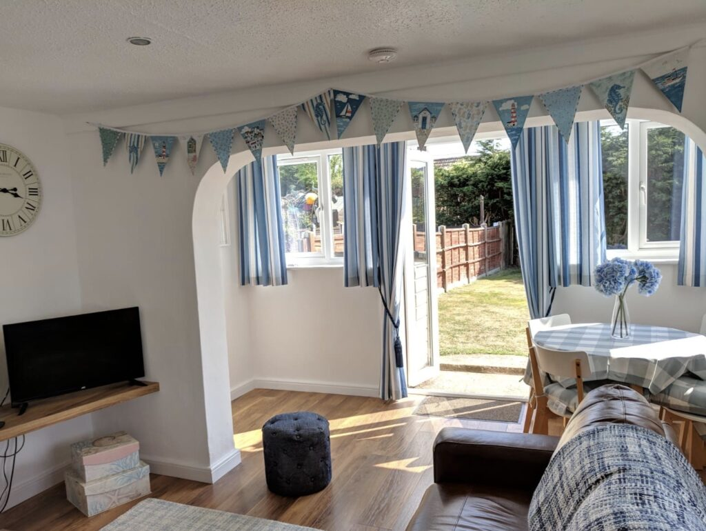 Inside of a holiday house in Norfolk with sofas, a TV and blue bunting on the ceiling and blue curtains