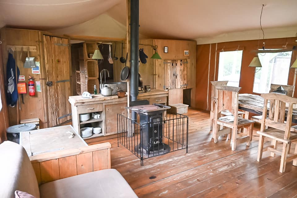 inside view of feather down glamping lodge with a sofa, log burner and wooden kitchen