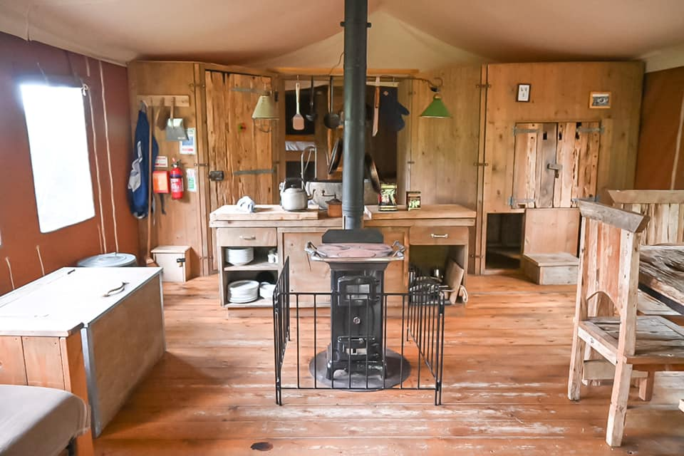 Inside of Layer Marney Glamping lodges with a log burner in view and the kitchen and bedrooms behind