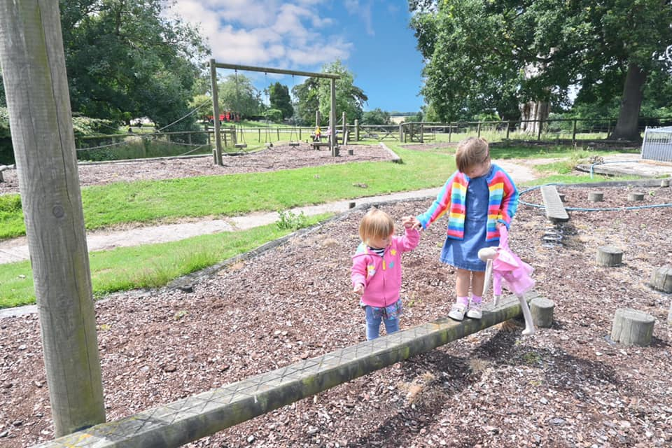 children in the park, one walking across a balance beam and the other holding the girls hand. There is wood chip on the floor and other climbing apparatus in the distance
