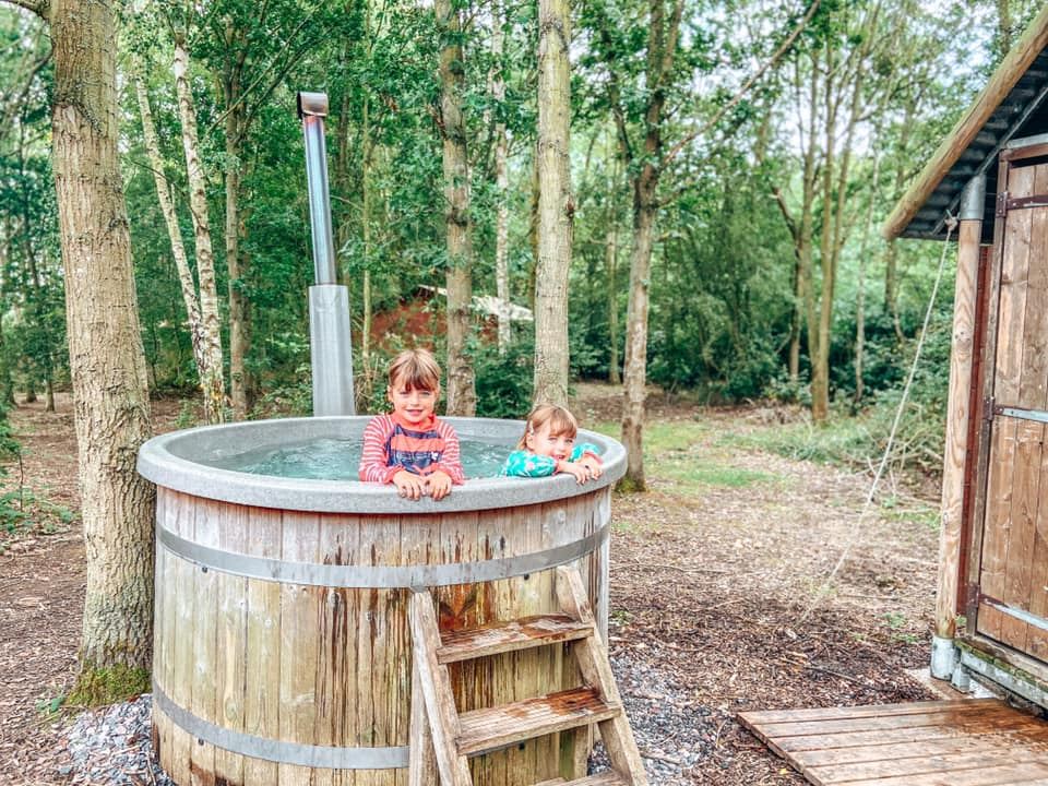 two children in a hot tub in the middle of the woods