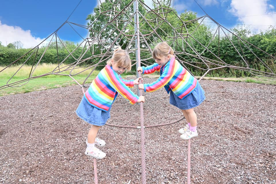two children climbing up a spiders climbing frame waring rainbow cardigans