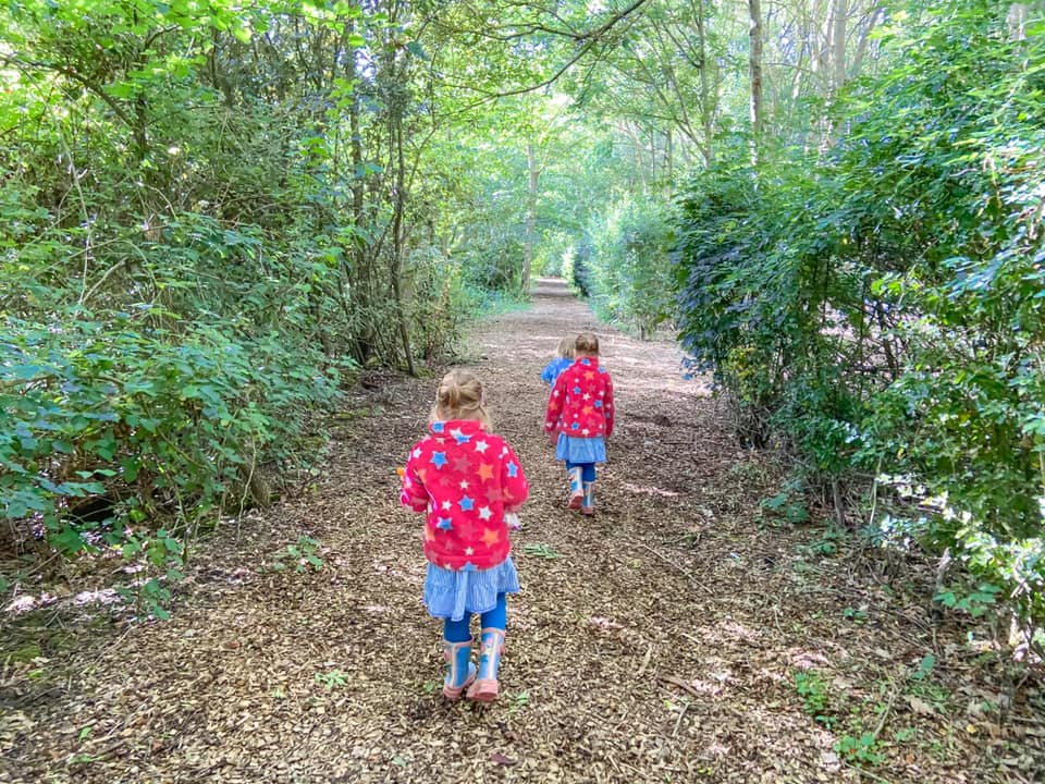 three girls walking in the woods down a wood chip path