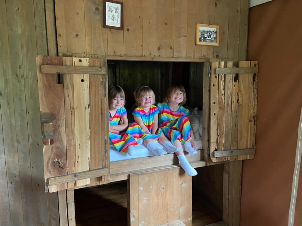 three children in rainbow dresses sitting in the cupboard bed at feather down glamping lodge