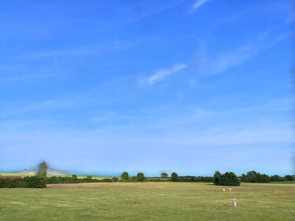 green fields and blue sky with children running in the distance