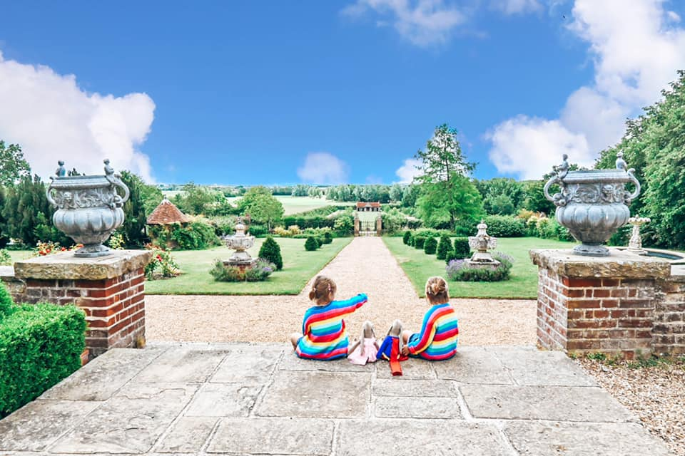 two girls in rainbow cardigans looking out over Layer Marney grounds