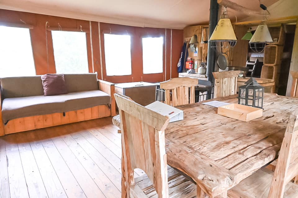 Inside view of glamping lodge with wooden table and chairs, log burner and kitchen with the bedrooms in the distance