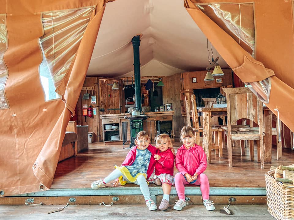 three children sitting in the opening of a glamping tent