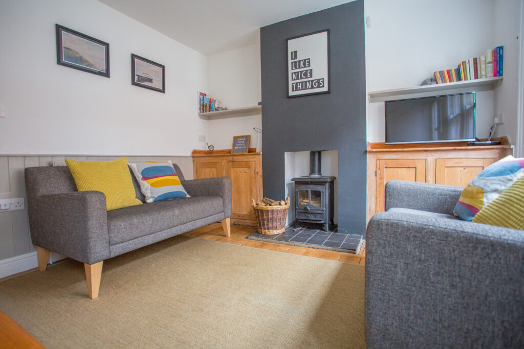 grey sofas say on a light wooden floor with a beige rug over the top. A black log burner sitting in the middle with a white picture on the wall