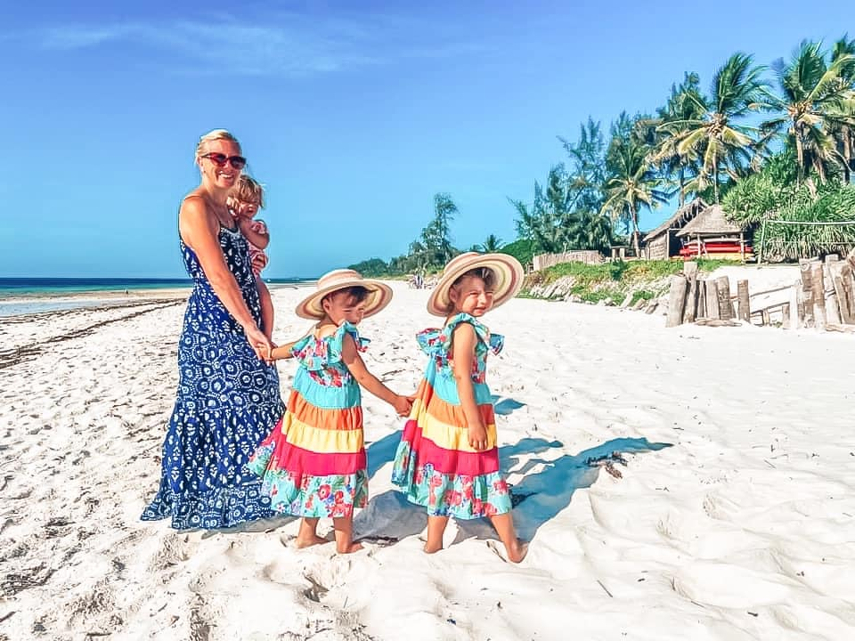 mummy walking on Watamu beach holding a baby with twin girls in rainbow dresses holding hands