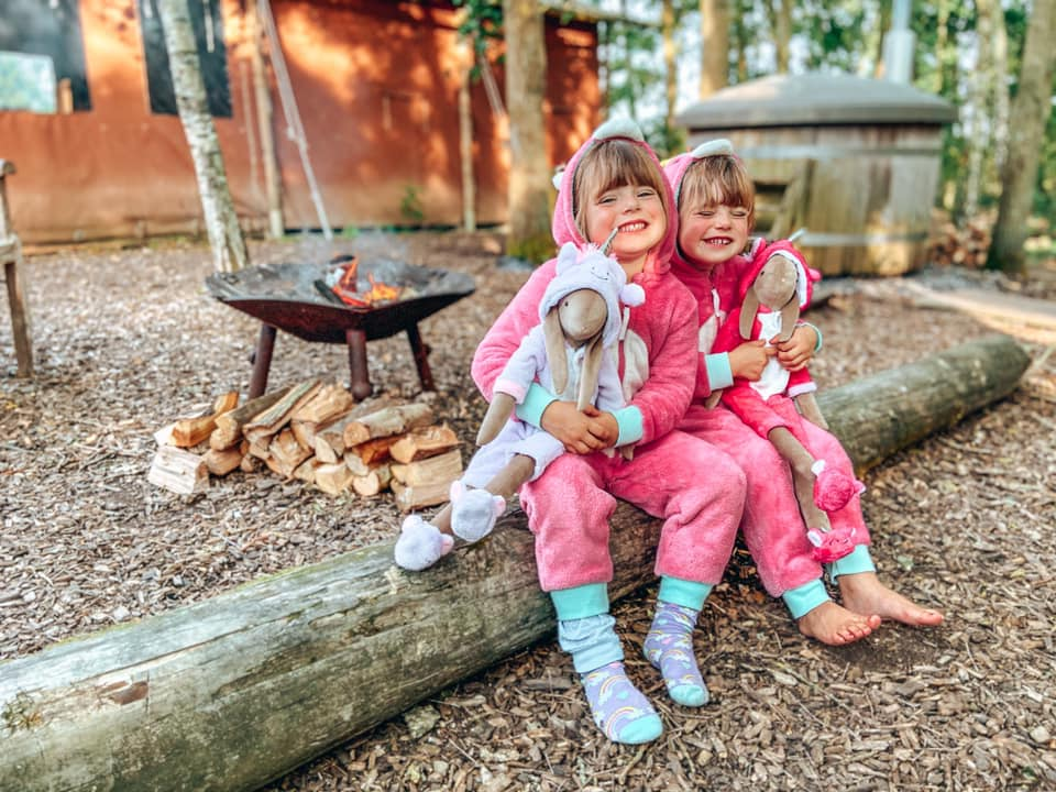 two children sitting on a log with a campfire lit behind them and the hot tub in the distance