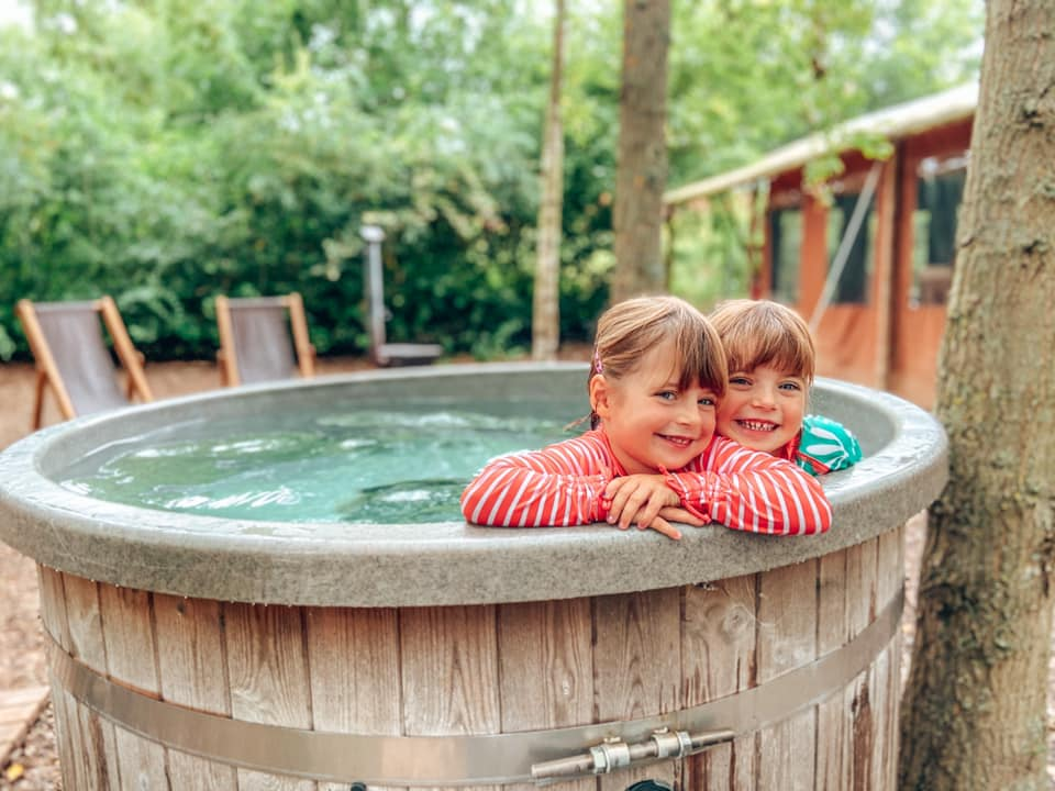 two children in a wooden hot tub in the woods which is situated next to the glamping tent