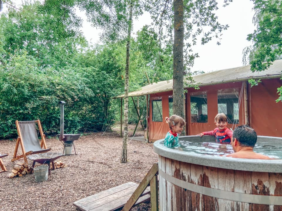 two children and a man in a hot tub in the woods with a feather down glamping lodge and fire pit