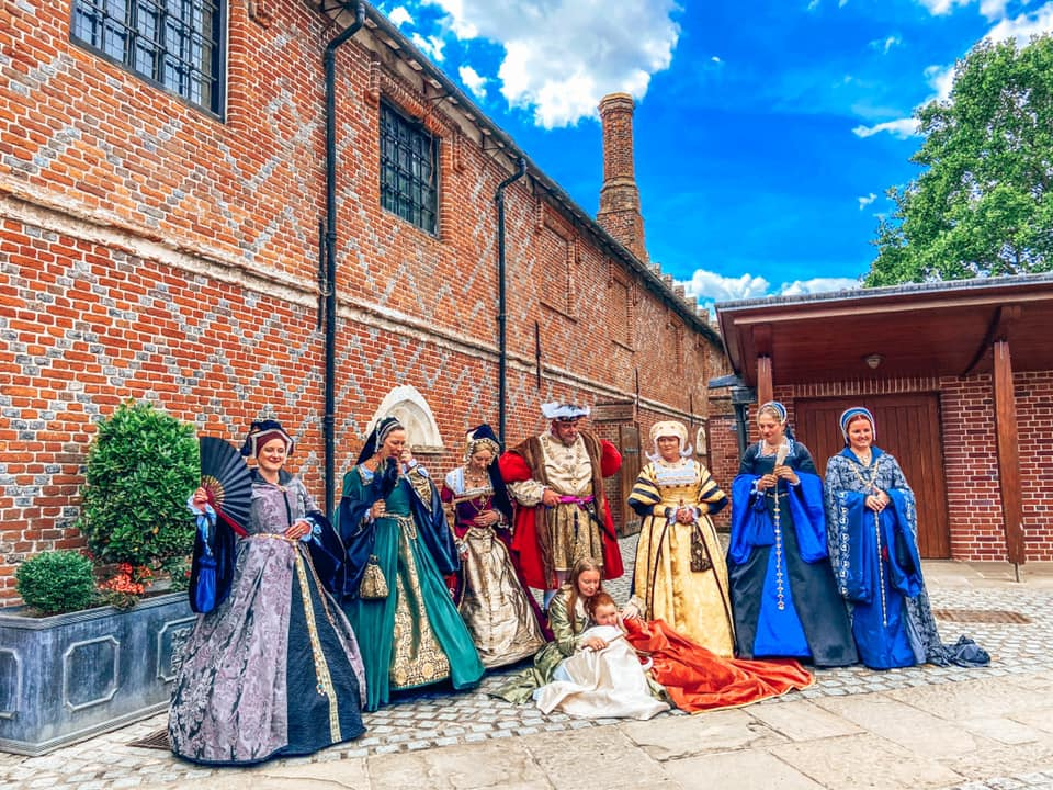 nine people dressed in elegant tudor costumes with king henry the VIII at Layer Marney tower in Essex