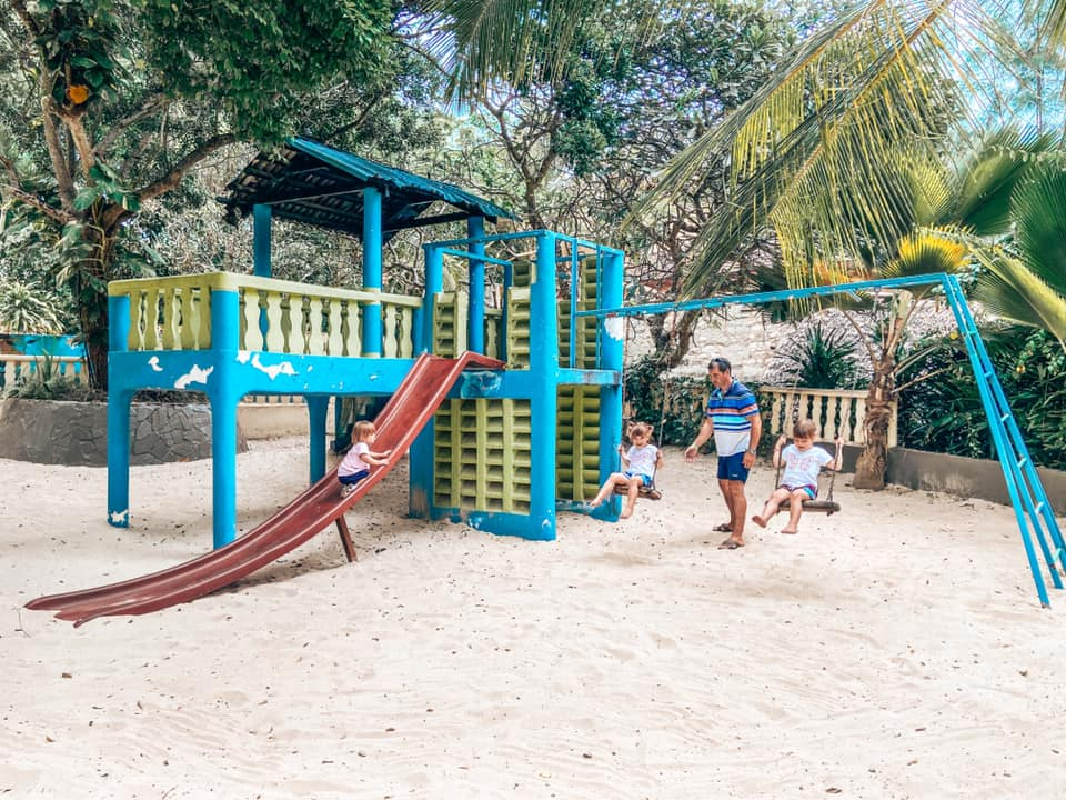 Three children playing on the swings in an adventure playground at Turtle Bay Resort. There is a large red slide and a playhouse at the top