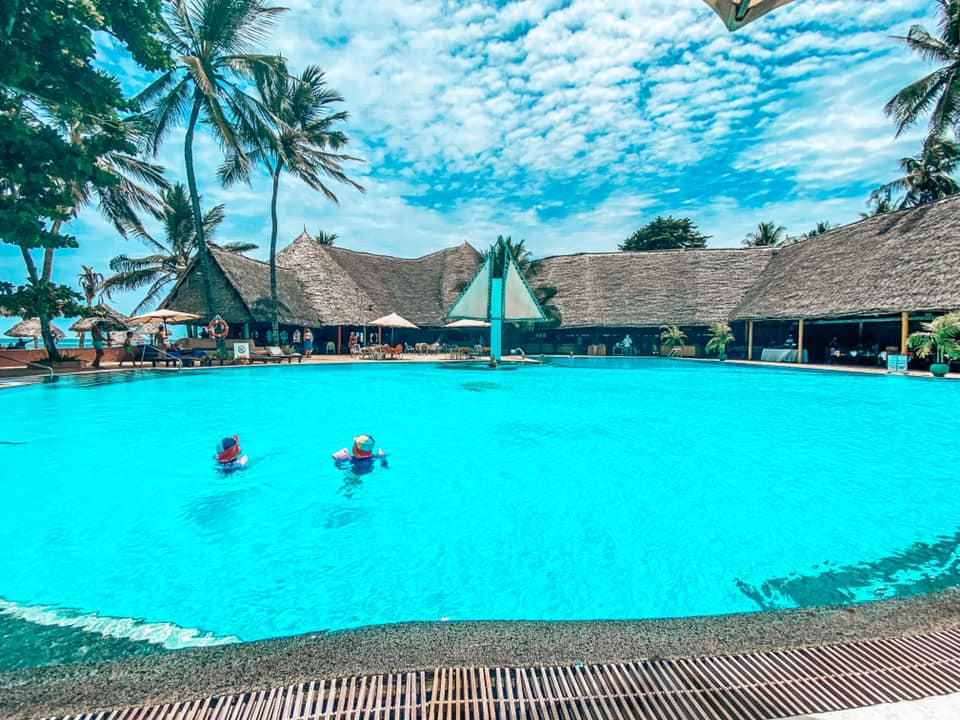 Swimming pool at Turtle Bay Kenya with two people swimming and a covered dining area surrounding the edge of the pool