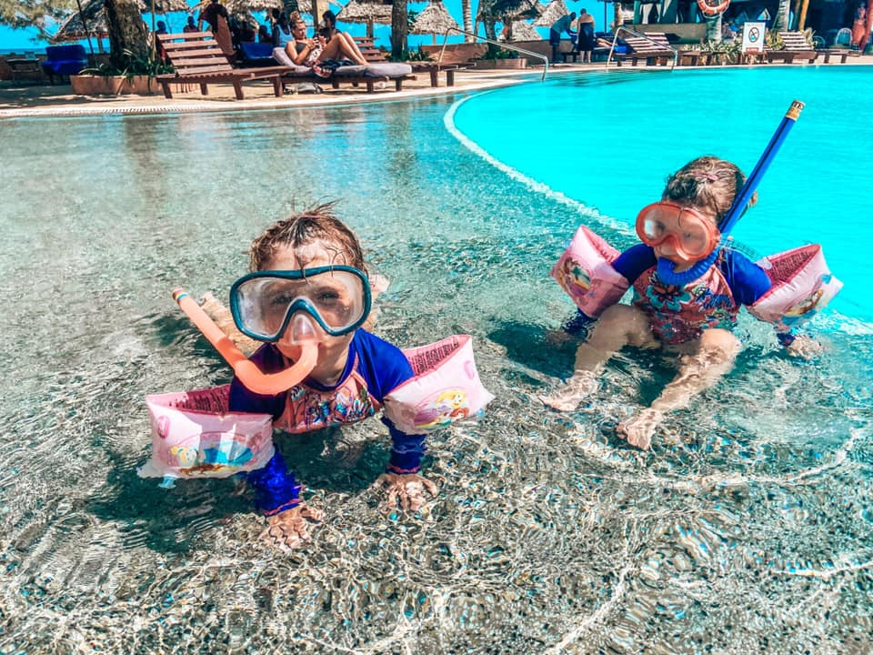 Two girls with snorkel gear on in the main swimming pool at turtle bay resort