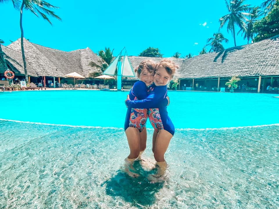 two young children in blue swimming costumes juggling on the edge of a large swimming pool at Turtle Bay