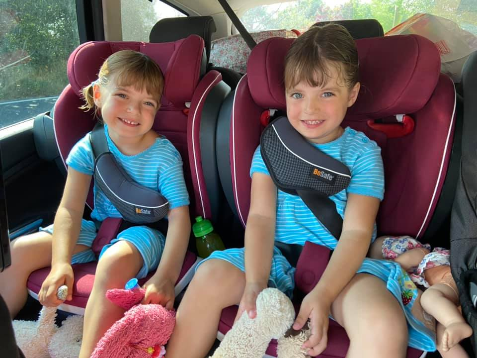 Two girls in blue dresses sitting in stage three red car seats