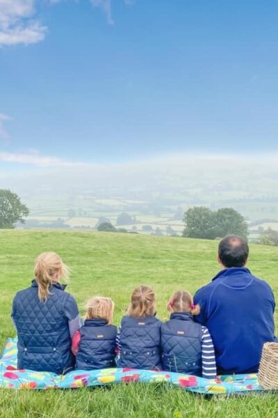 family of 5 sitting on a pacmat picnic rug looking out to the welsh hills