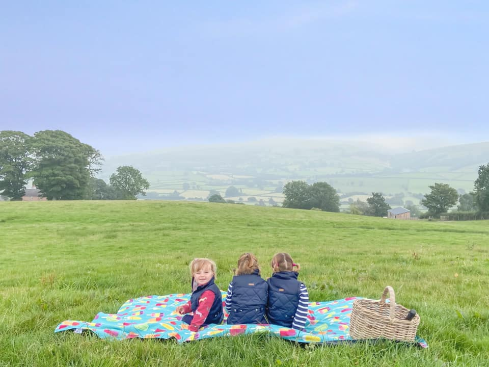 three girls in blue, sitting on the pacmat rug in the middle of the field