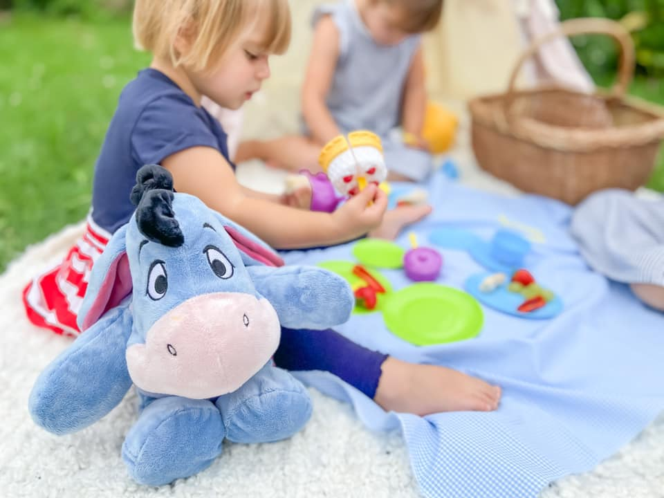 Eeyore from Winnie the Pooh sat next to a toddler who is eating a picnic