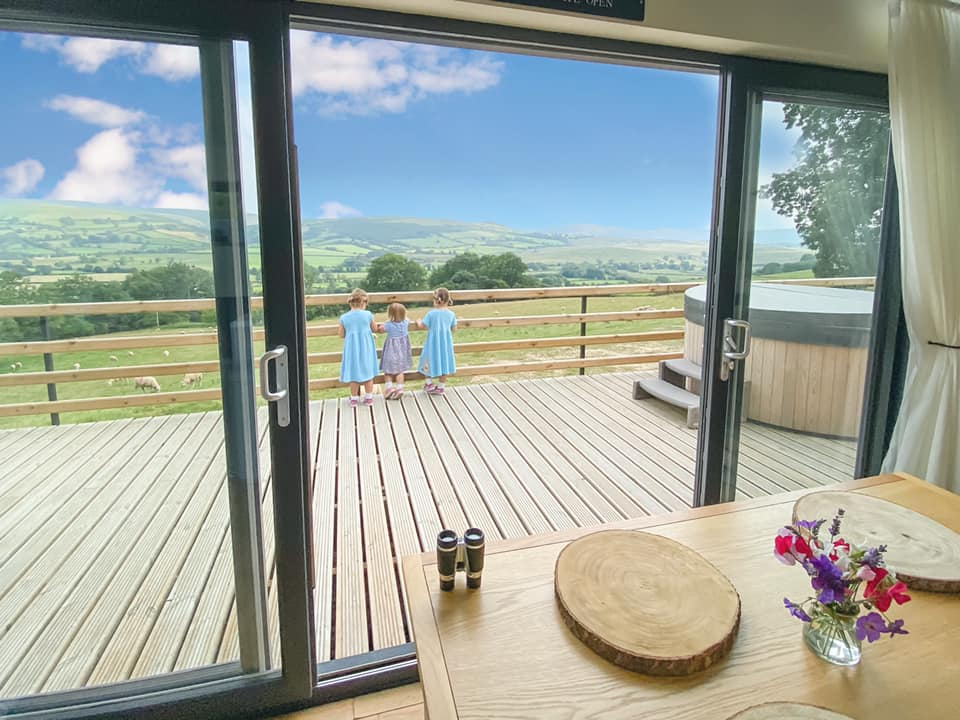 Large double doors looking to the outside are of Penlan Lodges. The hot tub is in view to the right and green rolling hills all around with two girls in blue dresses standing