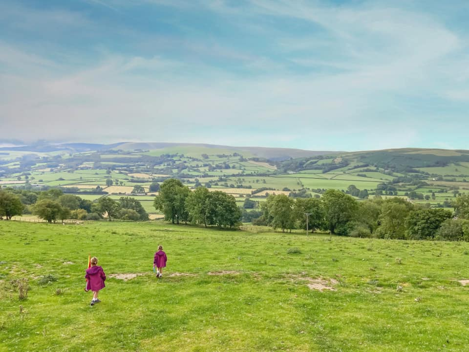 two children in purple coats running down the hill at Penlan lodges