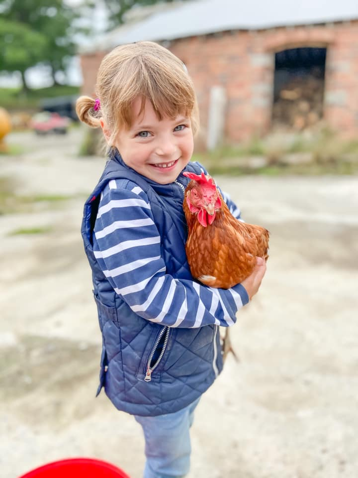 Young girl wearing a blue and white jumper, smiling holding a chicken