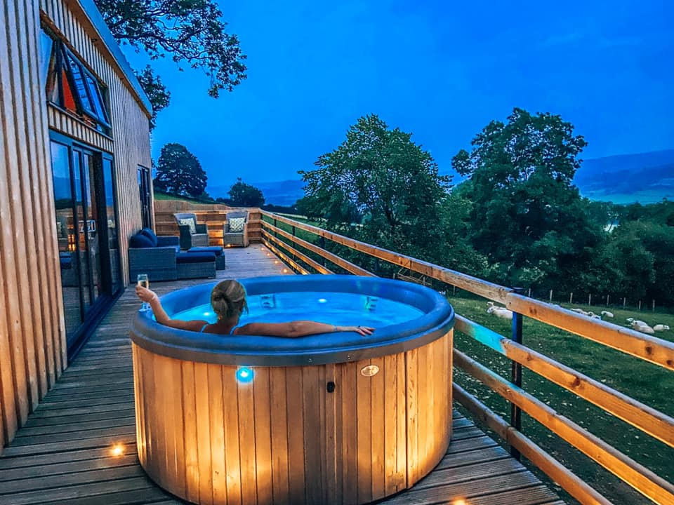 The hot tub at Penlan lodges after dark looking out over the fields