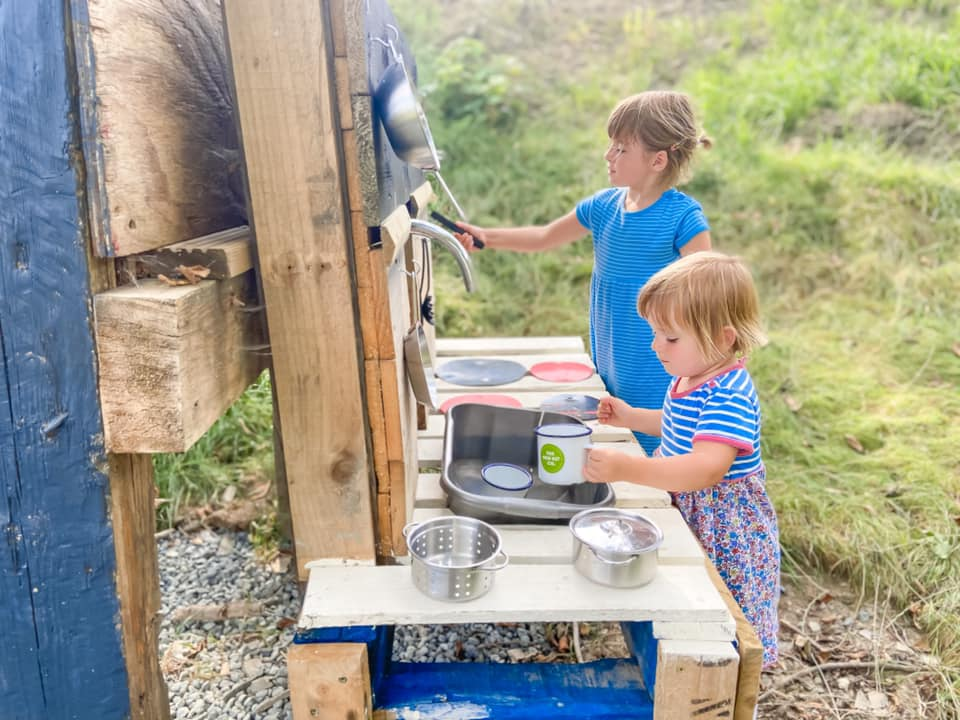 two young girls playing in the mud kitchen at Penlan Lodges