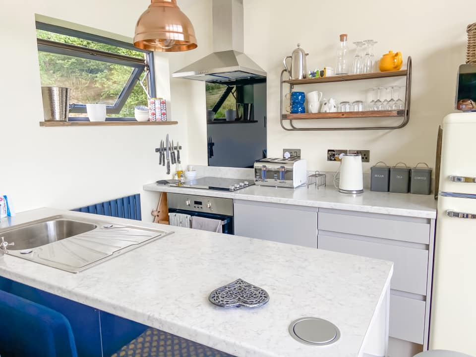The kitchen at Penlan lodges with a white worktop, silver sink and cooker with shelves up on the wall
