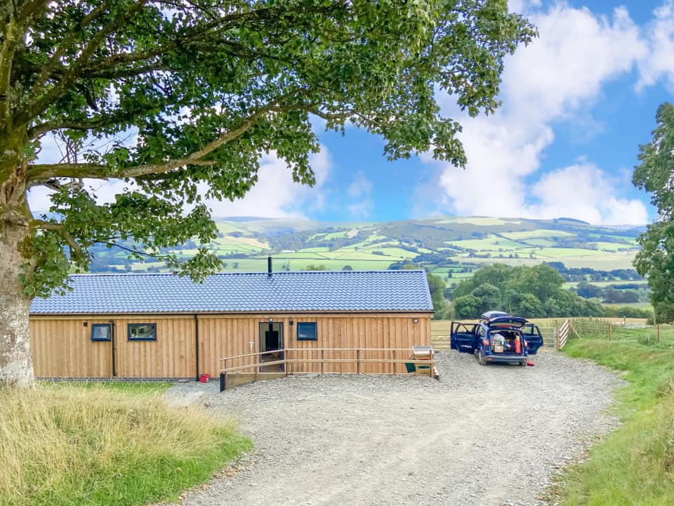 Timber lodge overlooking green rolling hills in Wales