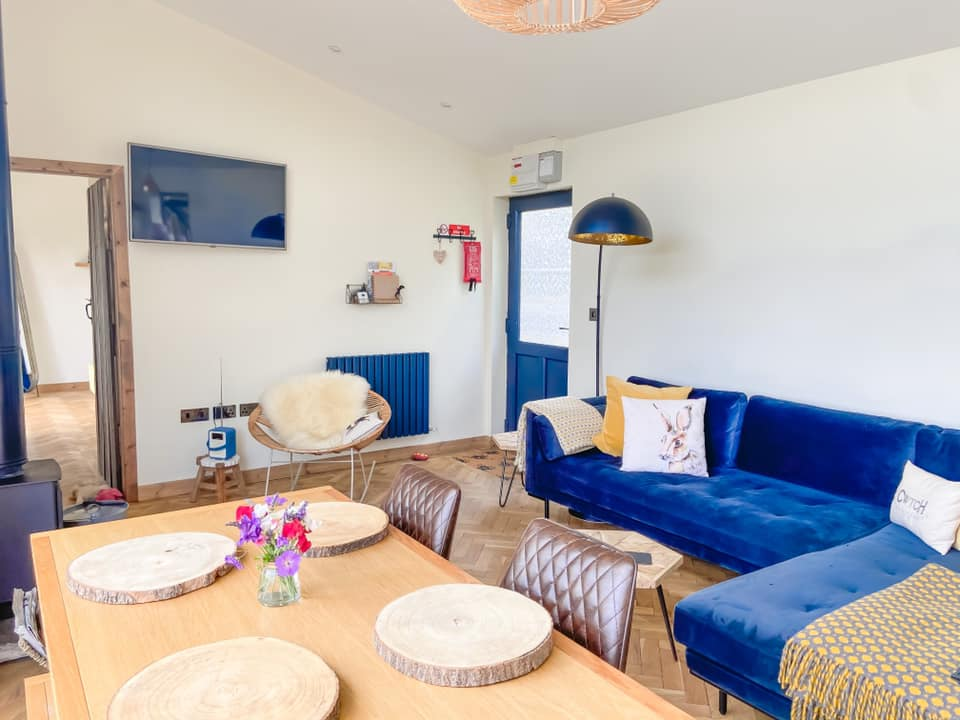 Lounge area at Penlan with a navy velvet L shaped sofa, and wooden table with log type place mats
