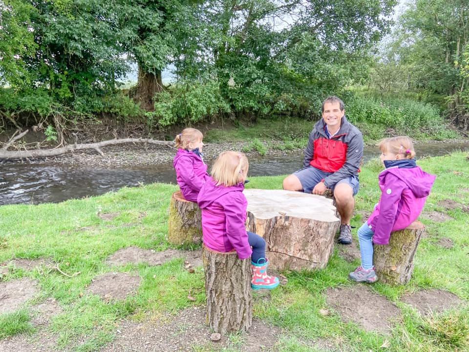 three young girls in purple coats and a daddy sat on logs besides a river