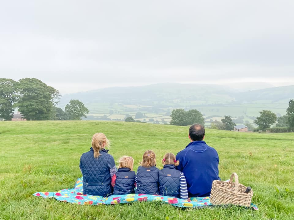 family of 5, 2 adults and 3 children sitting on a rug looking out the the Penlan valley