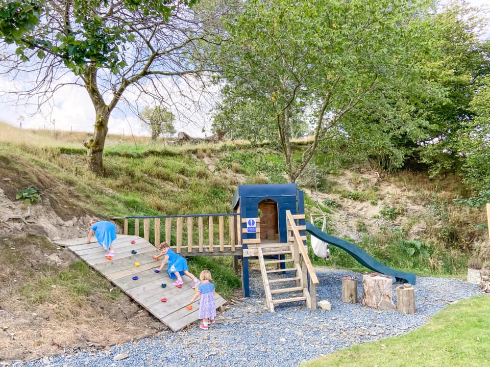 Three children playing on the play area at penal lodges. A small climbing wall, play house and green slide