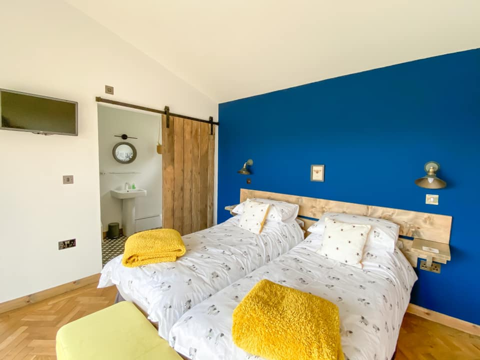 Twin bedroom at Penlan lodges with sheep beeding and mustard blankets on the bottom of the bed. to the left is an ensuite bathroom with the door open.