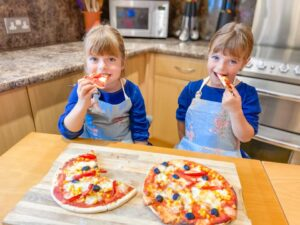 two girls sitting at a wooden table with pizza bases in front of them and they are eating their Red pepper and Sweetcorn pizza